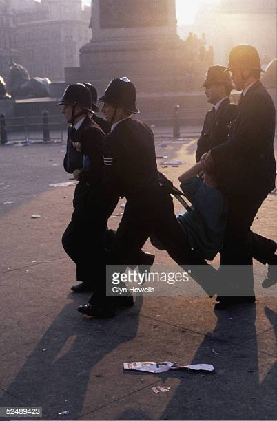 Police officers carry away a protester during the Poll Tax riot in Trafalgar Square London 31st March 1990