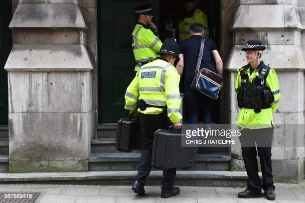 Police officers carry cases into Granby House following a raid close to Manchester Piccadilly railway station in Manchester on May 24 as their...