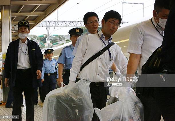 Police officers carry evidence from a Nozomi 255 bullet train or 'shinkansen' stopped at the Odawara station on June 30 2015 after an apparent...