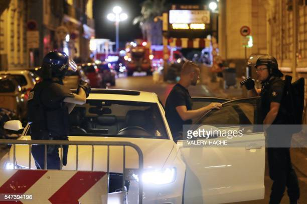 TOPSHOT Police officers carry out checks on vehicles in the centre of French Riviera town of Nice after a truck drove into a crowd watching a...