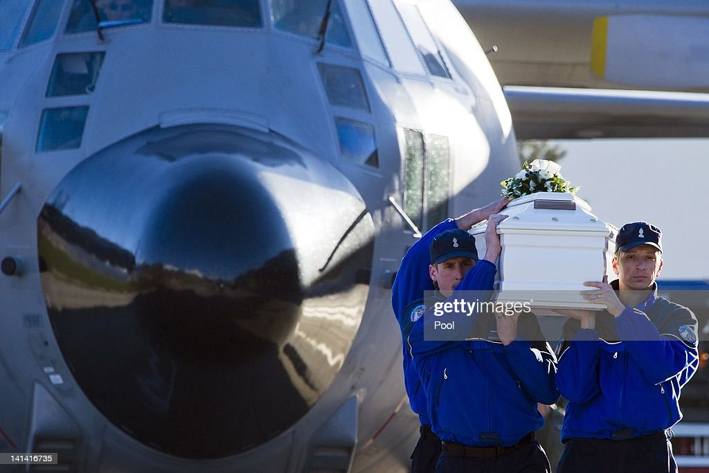 Police officers carry the coffin of one of the 28 victims of Sierre's coach crash to load it into a Belgian military cargo aircraft at Sion airport on March 16, 2012 in Switzerland. The accident occurred when a school bus carrying 11 -12 year old children back to Belgium from a skiing holiday, crashed into a tunnel wall, killing 28 of the 52 passengers. Belgium is holding a day of national mourning today to remember the victims of the crash.