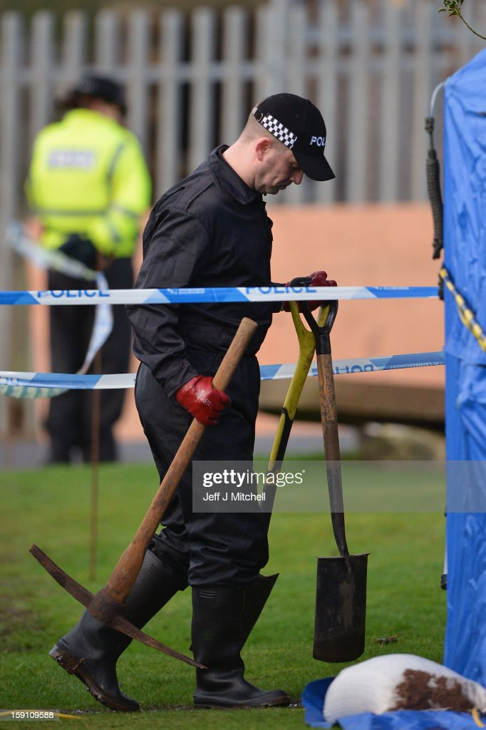 Police officers carrying spades and pick axes arrive at Monkland Cemetery to start examining a burial plot on January 8, 2013 in Coatbridge, Scotland. Forensic specialist will exhume remains at a grave in North Lanarkshire in search for the body of 11 year old school girl Moria Anderson, who went missing, presumed murdered, in 1957.