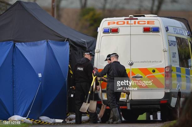 Police officers carrying spades and pick axes arrive at Monkland Cemetery to start examining a burial plot on January 8 2013 in Coatbridge Scotland...