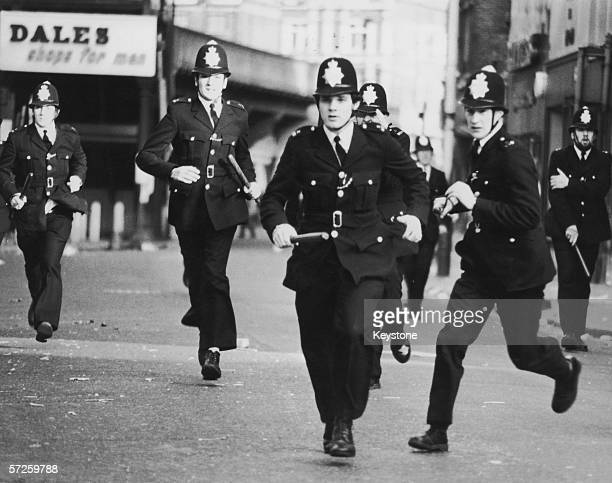 Police officers charge on the second day of rioting in Brixton London 13th April 1981