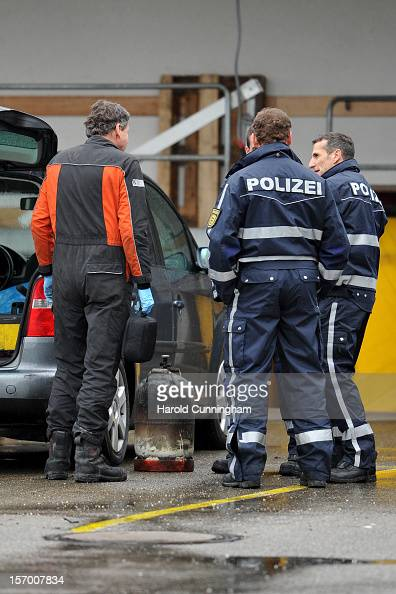Police officers chat next to a gas bottle taken for inspection from a Caritas employment facility for handicapped where a fire killed 14 people on...