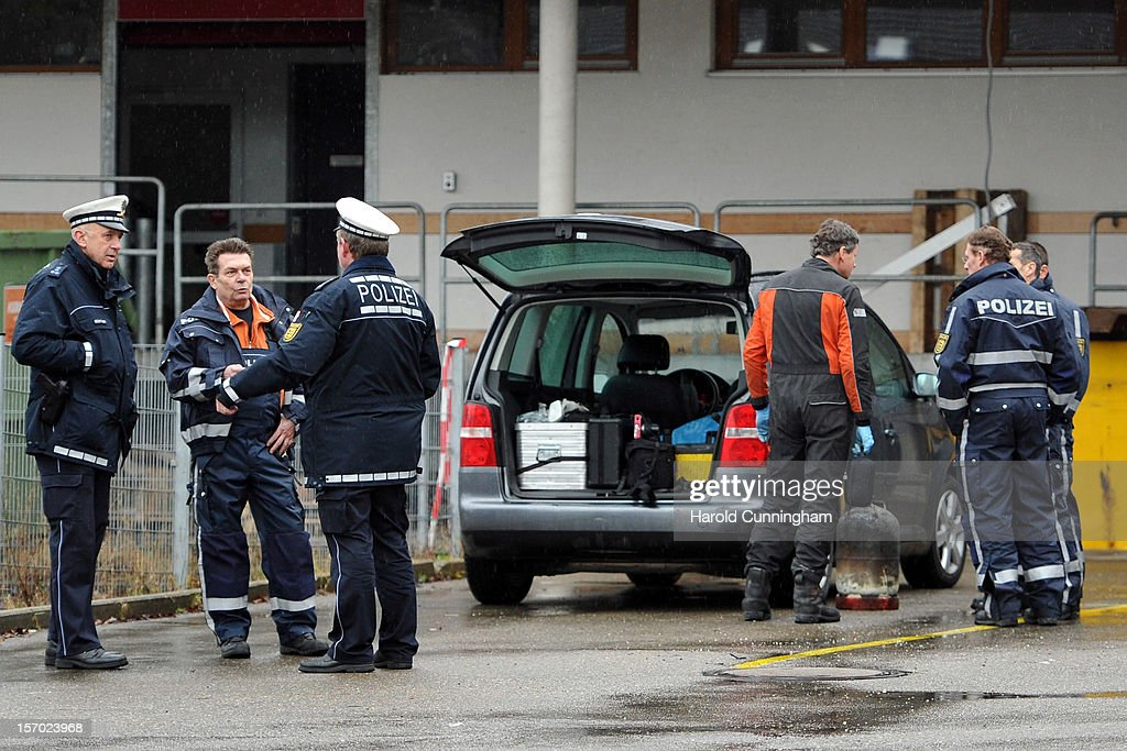 Police officers chat next to a gas bottle taken for inspection from a Caritas employment facility for handicapped where a fire killed 14 people on November 27, 2012 in Titisee-Neustadt, Germany. The fire was reportedly caused by an explosion at the facility, where approximately 120 people with disabilities are employed in light manufacturing.