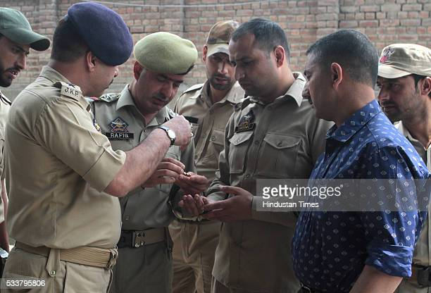 Police officers check bullets after two policemen were killed by suspected militants in a shootout in Zadibal in the old part of the city on May 23...