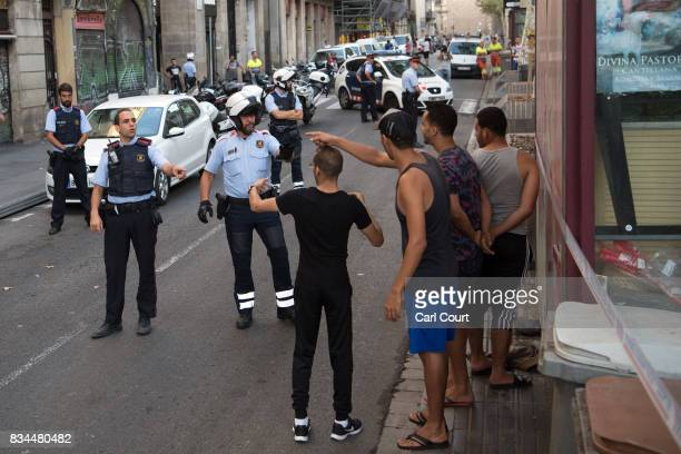 Police officers check the identity of a group of men on Las Ramblas following yesterday's terrorist attack on August 18 2017 in Barcelona Spain...