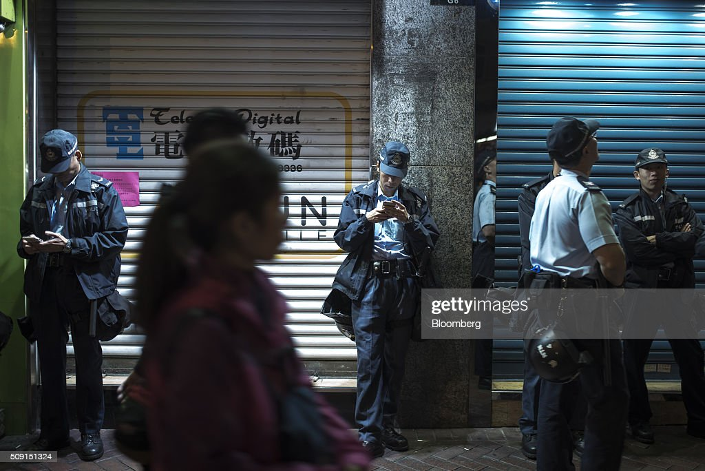 Police officers check their mobile devices as they stand beside shuttered stores during the Chinese New Year celebrations, following the previous night's rioting in Kowloon's Mong Kok district, in Hong Kong, China, on Tuesday, Feb. 9, 2016. Police Commissioner Stephen Lo Wai-chung told reporters that officers would remain vigilant during celebrations to mark Chinese New Year, one of the most important events on Hong Kong's calendar. Photographer: Xaume Olleros/Bloomberg via Getty Images