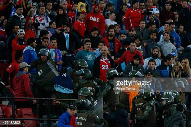 Police officers clash with Chilean fans during the 2015 Copa America Chile Final match between Chile and Argentina at Nacional Stadium on July 04...