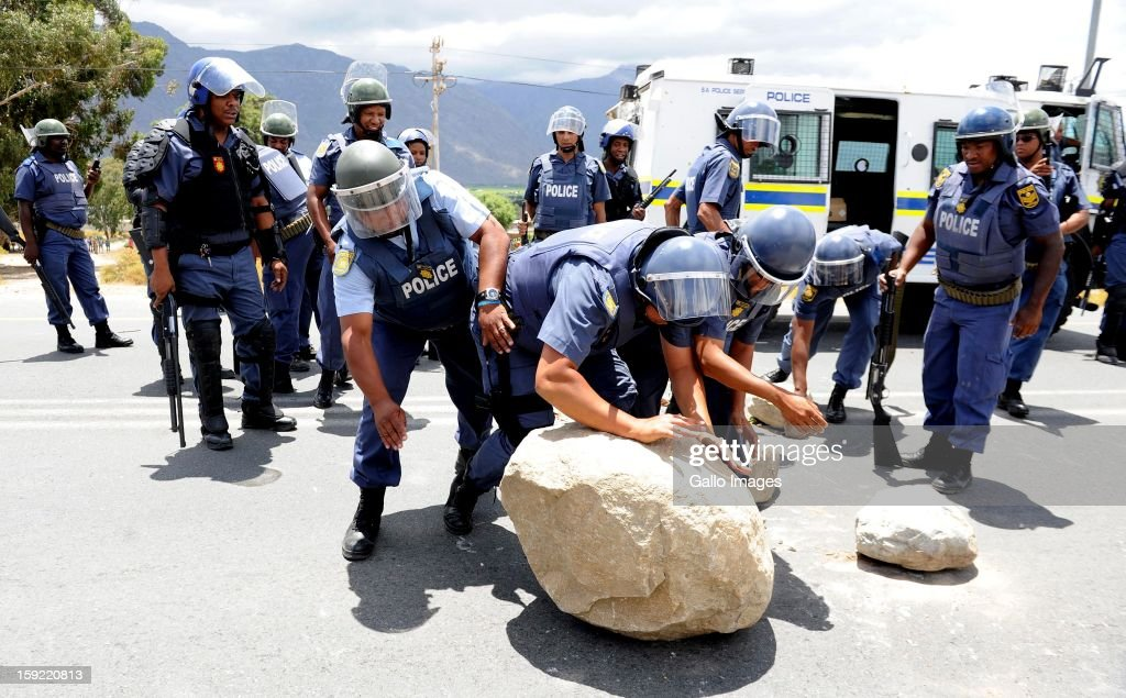 Police officers clear up the N1 at the De Doorns protest on January 9, 2013, in Cape Town, South Africa. The farm workers shut down the N1 by lighting tires on fire and placing large rocks on the road.