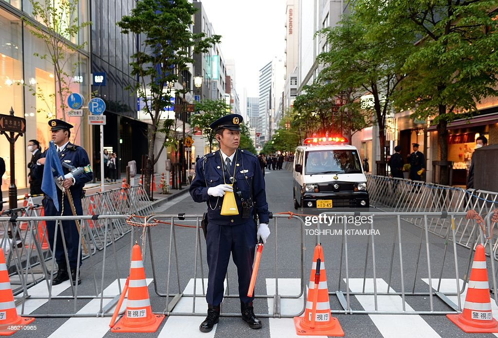 Police officers close the road connecting to the 'Sukiyabashi Jiro' sushi restaurant at Ginza shopping district in Tokyo on April 23, 2014, hours before US President Barack Obama's visit. Obama will reportedly dine at a tiny Tokyo sushi restaurant, a place with three coveted Michelin stars but only a handful of seats, ruled with an iron rod by its redoubtable 88-year-old owner, Jiro. Obama will come to Tokyo for a three-day visit from April 23 for and will have dinner with Japanese Prime Minister Shinzo Abe. AFP PHOTO / TOSHIFUMI KITAMURA