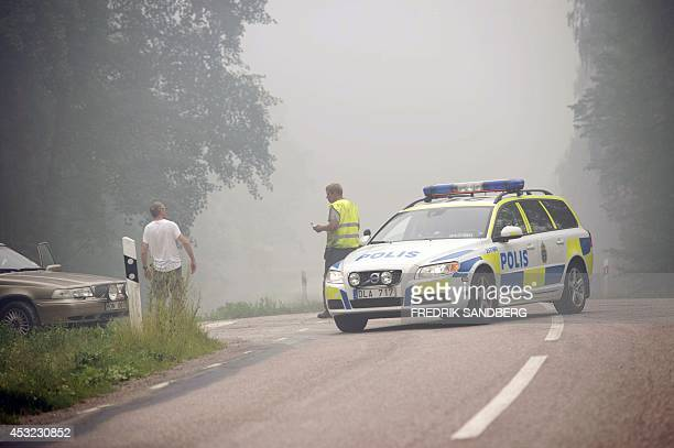 Police officers close the road south of Norberg town in Central Sweden as a forest fire rages on August 5 2014 The fire covering thousands of...