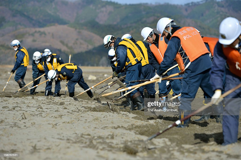 15 police officers committed to search the missings continues to dig the 106 hectare area near Okawa Elementary School on December 11, 2012 in Ishinomaki, Miyagi, Japan. 70 out of 108 pupils of the school were killed by the earthquake triggered tsunami last year and the searching work continues on the 21 months anniversary day.