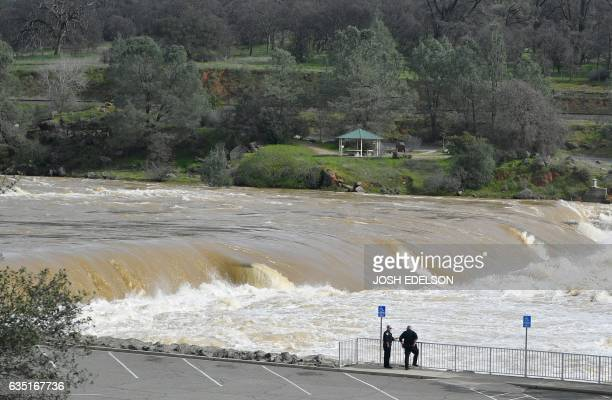 Police officers confer as the Oroville Dam releases water down a spillway as an emergency measure in Oroville California on February 13 2017 Almost...
