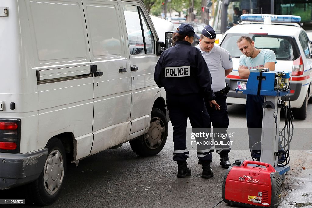 Police officers control a motorist and his van on July 1, 2016 in Paris as part of the anti-pollution measures aimed at punishing road transports registered before 1997 that are forbidden to be driven during the week. Nearly thirty police officers stood guard on the morning of July 1, in the main squares of Paris to control and raise awareness among the drivers about the new measures concerning road transports adopted by the city and effective from today. Those first controls, mostly to inform and without verbalisation, were organised by the police headquarters and Paris city hall. / AFP / FRANCOIS