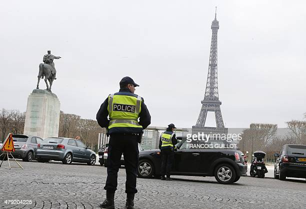 Police officers control cars in front of the Eiffel Tower in Paris on March 17 2014 as Paris resorted to drastic measures to curb soaring pollution...