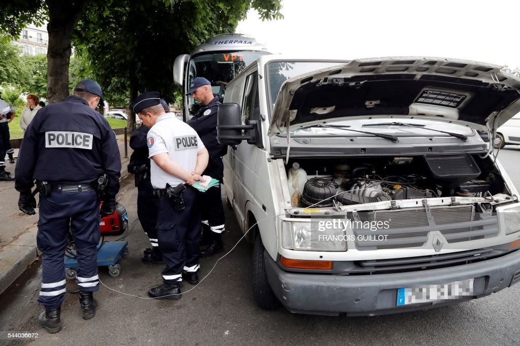 Police officers control the pollution level of a van on July 1, 2016 in Paris as part of the anti-pollution measures aimed at punishing road transports registered before 1997 that are forbidden to be driven during the week. Nearly thirty police officers stood guard on the morning of July 1, in the main squares of Paris to control and raise awareness among the drivers about the new measures concerning road transports adopted by the city and effective from today. Those first controls, mostly to inform and without verbalisation, were organised by the police headquarters and Paris city hall. / AFP / FRANCOIS