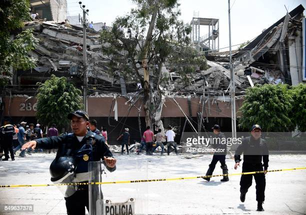TOPSHOT Police officers cordon the area off after a building collapsed during a quake in Mexico City on September 19 2017 A powerful earthquake shook...