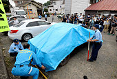 Police officers cover a car suspect Satoshi Uematsu drove to turn in with a blue tarp at Tsukui Police Station on July 26 2016 in Sagamihara Kanagawa...