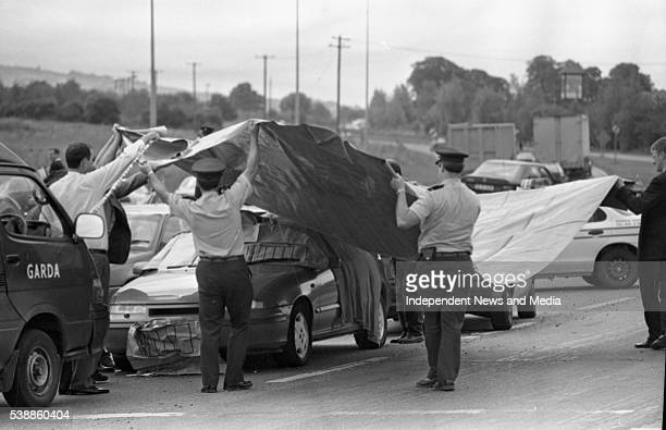 Police officers cover Sunday Independent newpaper journalist Veronica Guerin's car in which she was murdered on the Naas Road near Newlands Cross...