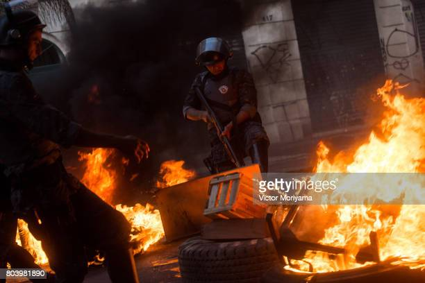 Police officers deal with a fire started by protesters linked to the social movements Front for Housing Struggle in protest against the Social...