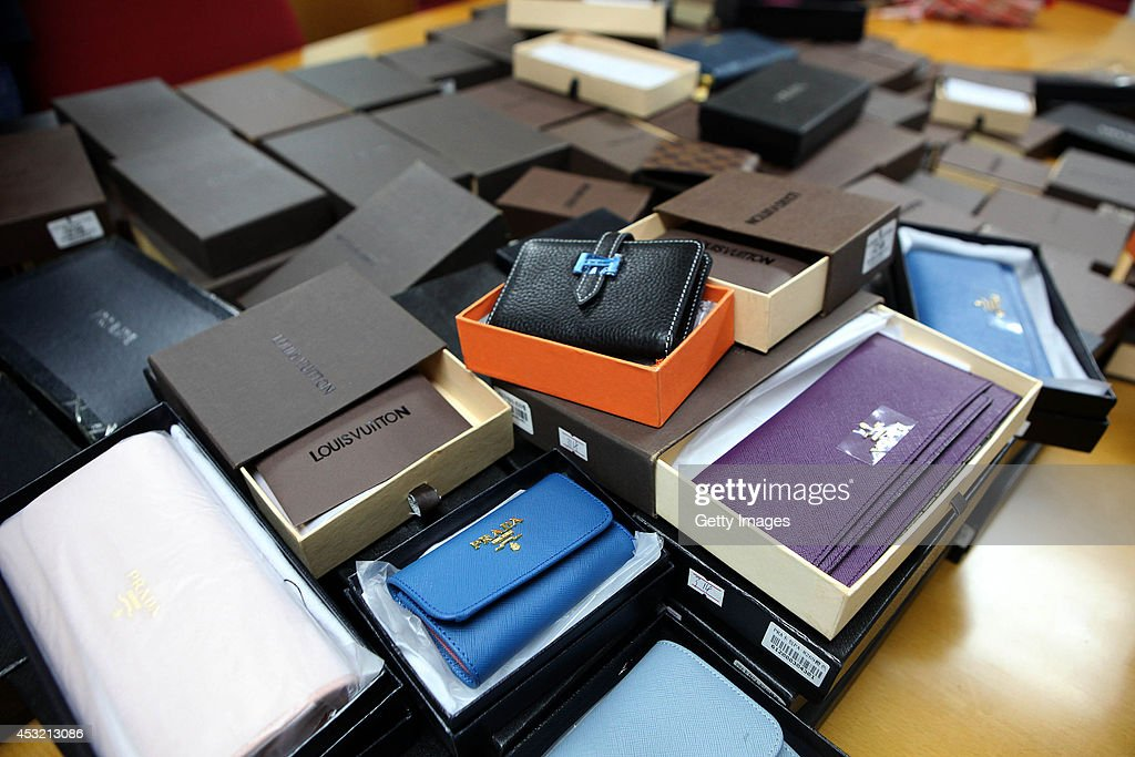 Police officers deal with fake brandname items at a shop on August 4 2014 in Shenzhen China Shenzhen police seized a large number of fake brandname...