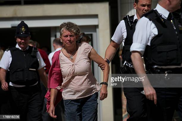 Police officers detain a climate protester after she and other demonstrators blocked the entrance to the office building housing PR company Bell...