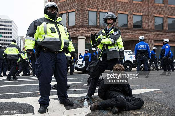 TOPSHOT Police officers detain a demonstrator before the inauguration of Presidentelect Donald Trump January 20 2017 in Washington DC Donald Trump...