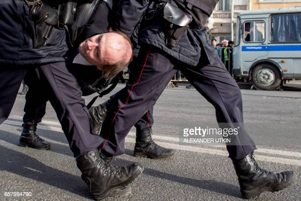 TOPSHOT Police officers detain a man during an unauthorised anticorruption rally in central Moscow on March 26 2017 Thousands of Russians...