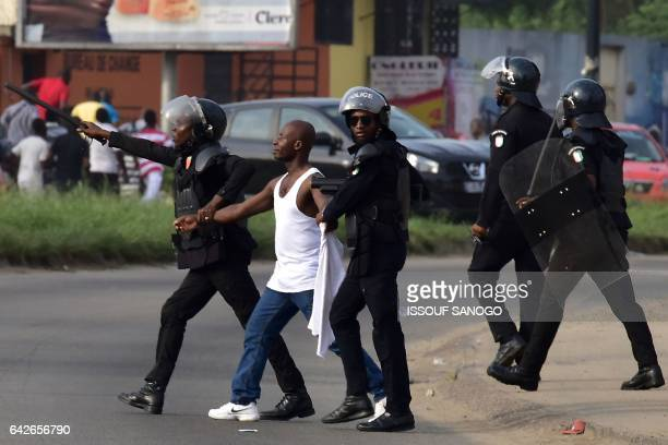 Police officers detain a protester during a demonstration of angry subscribers who invested in agribusiness companies on February 18 2017 in Abidjan...