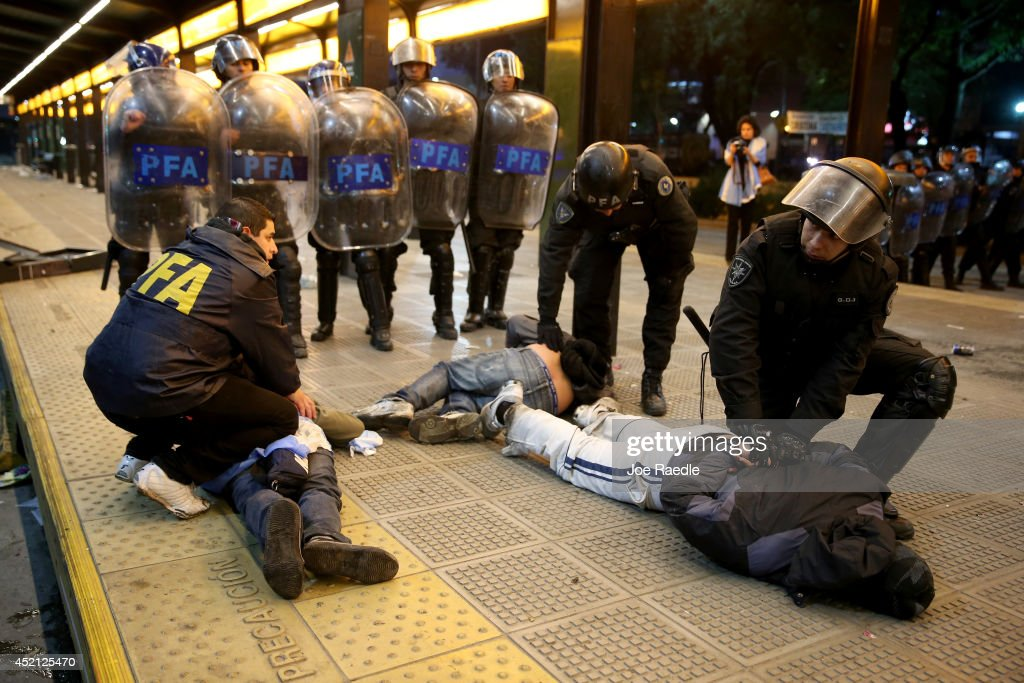 Police officers detain Argentine soccer fans caught after violence erupted near the Obelisco de Buenos Aires after their team lost to Germany 1-0 during the World Cup final on July 13, 2014 in Buenos Aires, Argentina. Germany won their 4th World Cup in the final match played in Rio de Janeiro.