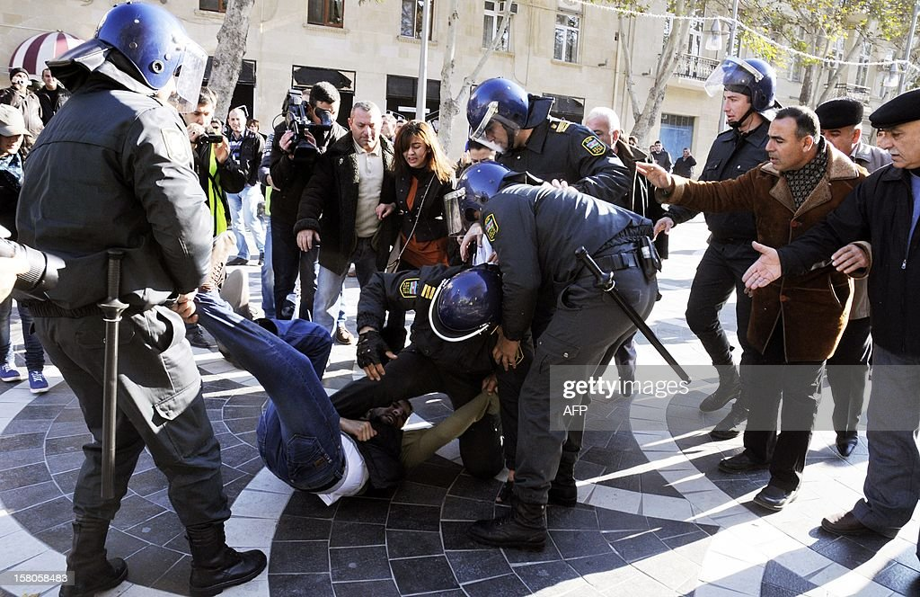 Police officers detain one of the opposition activists during an unauthorized rally to demand the resignation of President Ilham Aliyev at the Fountains Square in central Baku, the capital of Azerbaijan, on December 10, 2012. Police dispersed today the unauthorized pro-democracy protest.