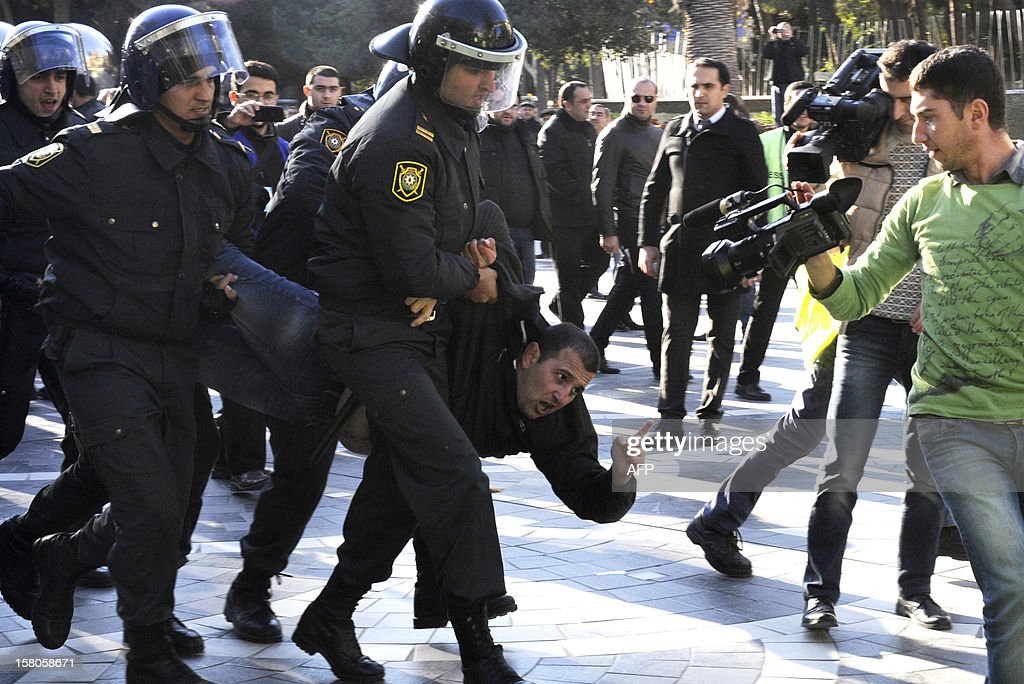 Police officers detain one of the opposition activists during an unauthorized rally to demand the resignation of President Ilham Aliyev at the Fountains Square in central Baku, the capital of Azerbaijan, on December 10, 2012. Police dispersed today the unauthorized pro-democracy protest. AFP PHOTO/ TOFIK BABAYEV