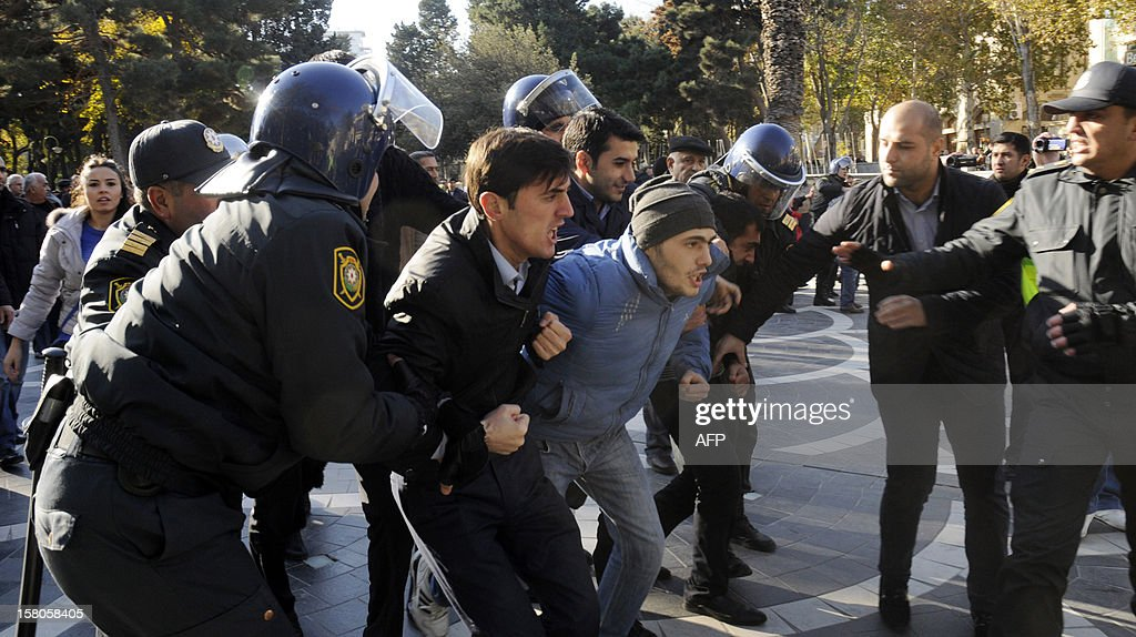 Police officers detain opposition activists as they try to hold an unauthorized rally to demand the resignation of President Ilham Aliyev at the Fountains Square in in central Baku, the capital of Azerbaijan, on December 10, 2012. Police disperced today the unauthorised pro-democracy protest. AFP PHOTO/ TOFIK BABAYEV
