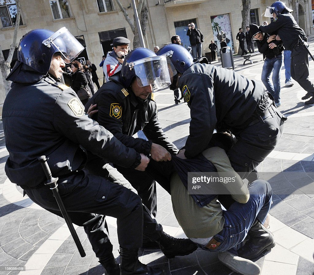 Police officers detain opposition activists as they try to hold an unauthorized rally to demand the resignation of President Ilham Aliyev at the Fountains Square in central Baku, the capital of Azerbaijan, on December 10, 2012. Police dispersed today the unauthorized pro-democracy protest. AFP PHOTO/ TOFIK BABAYEV