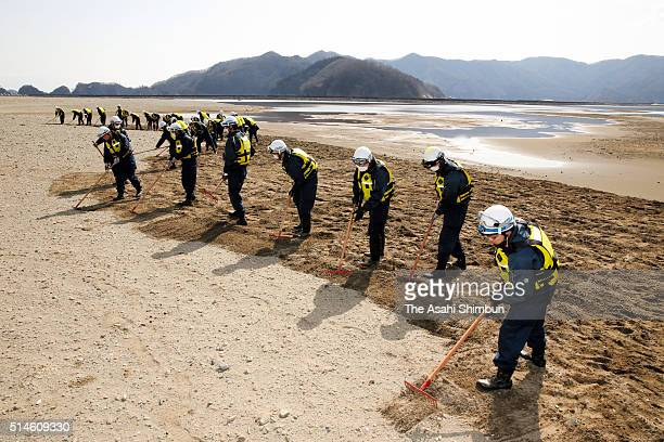Police officers dig the field to search clues of missings at Nagatsura area a day before the fifth anniversary of the Great East Japan Earthquake and...
