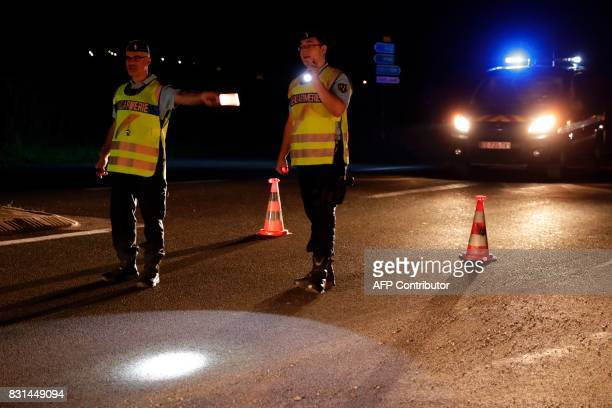 Police officers direct traffic on a road near the site where man smashed a car into a pizza restaurant in SeptSorts 55km east of Paris on August 14...