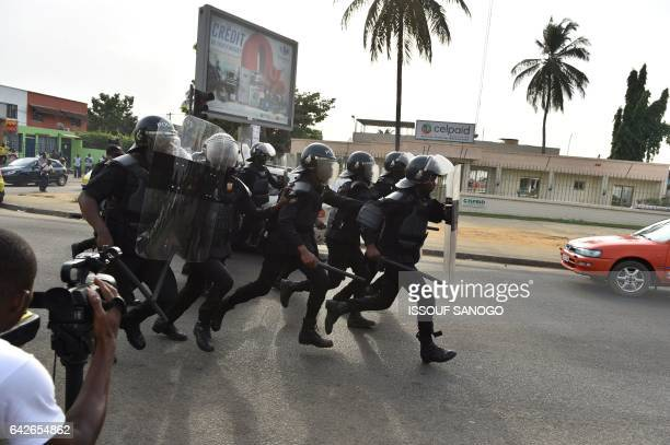 Police officers disperse protesters angry subscribers who invested in agribusiness companies during a demonstration on February 18 2017 in Abidjan...