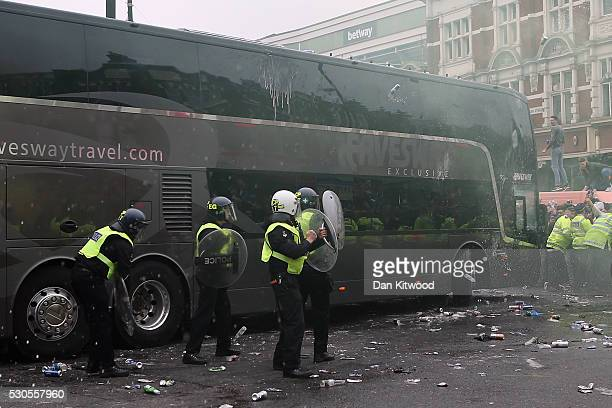 Police officers dodge projectiles as West Ham fans become violent and start throwing bottles at the bus carrying the Manchester United players to the...