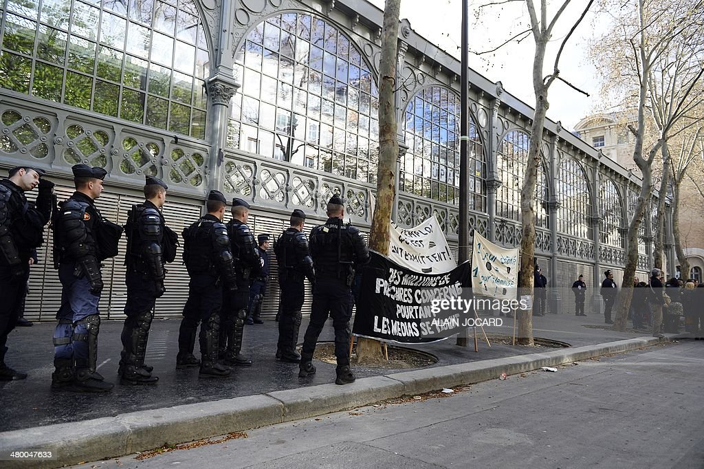 Police officers encircle the Carreau du Temple in Paris on March 22, 2014 as artists and technicians working in the entertainment industry occupy the building to protest against a planned reform of the rules regulating the unemployment benefits of temporary show business workers (intermittents).