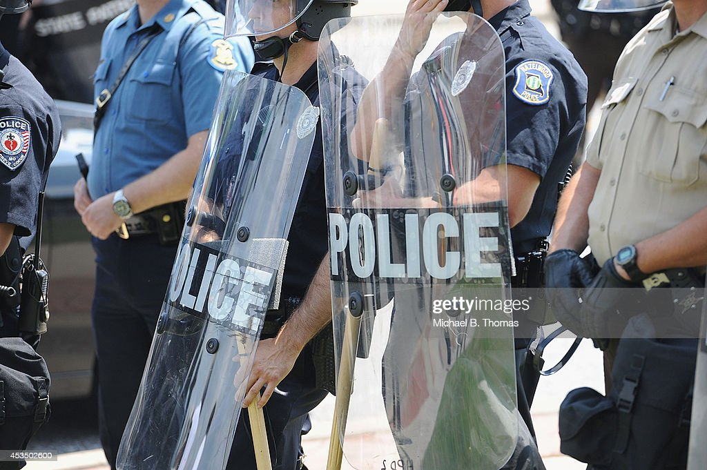 Police officers equipped in riot gear line up during a protest of the shooting death of 18yearold Michael Brown outside Ferguson Police Department...