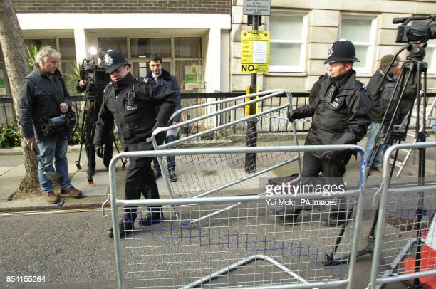 Police officers erecting barriers for the media outside the King Edward VII Hospital in London where Queen Elizabeth II is continuing her recovery...