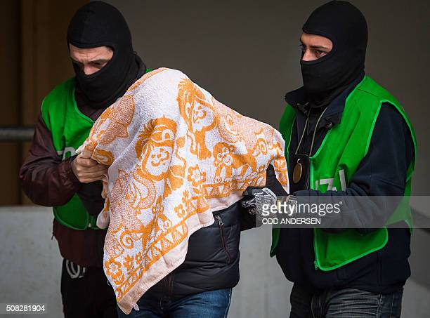 Police officers escort a man who was arrested in a flat during a raid on February 4 2016 in Berlin German police have arrested two Algerians they...