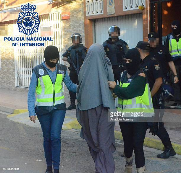 Police officers escort a woman accused of alleged connection with the Daesh terrorist group during her arrest in Xeraco in the province of Valencia...