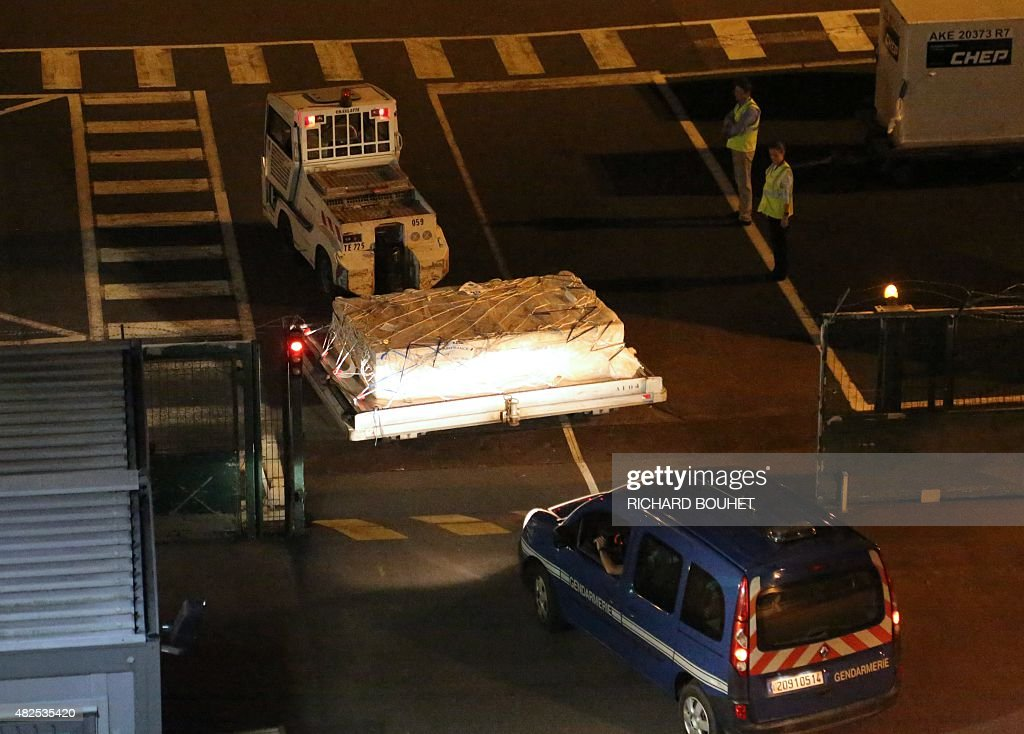 Police officers escort an airport vehicle transporting what is believed to be debris from a Boeing 777 plane that washed up on the Reunion Island at...