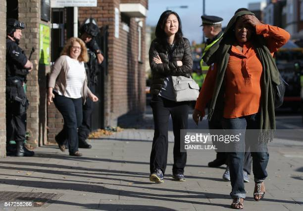 Police officers escort members of the public out of their inner cordon as they work near Parsons Green underground tube station in west London on...