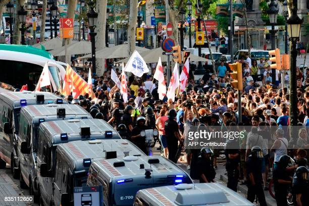 Police officers escort members of the Spanish rightwing group Falange carrying banners as they leave the Rambla after antifarright protesters...