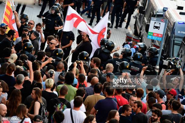 Police officers escort members of the Spanish rightwing group Falange as they leave the Rambla after antifarright protesters gathered to protest...