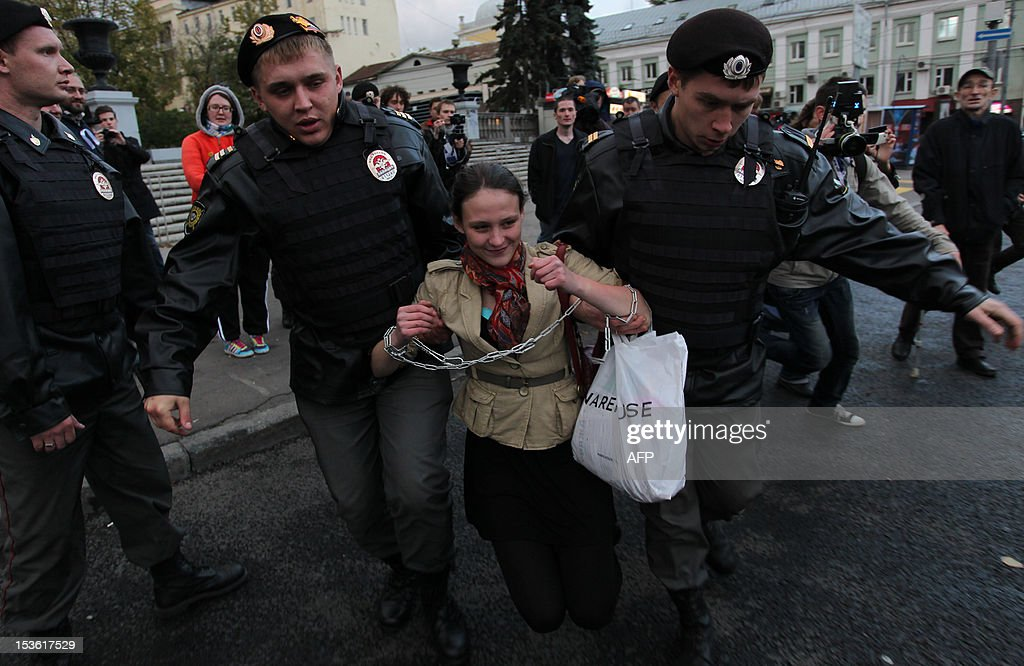 Police officers escort one of the demonstrators who were detained near the administration office of the Russian president in central Moscow, on October 7, 2012. The detained demonstrators tried to call Russia's President Vladimir Putin to go into retirement. The Russian strongman turned 60 today, the official retirement age in the country he has dominated for the past 12 years, as critics snickered that his image of an energetic, young macho leader no longer corresponds with his age.